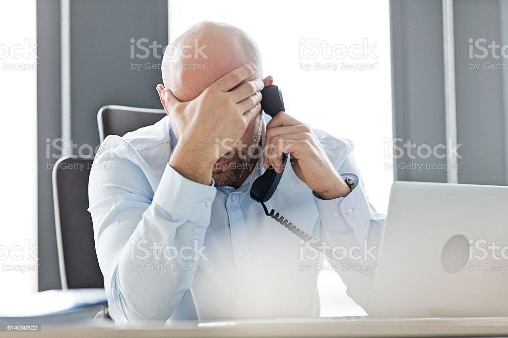 Tired mid adult businessman using landline phone at desk stock photo