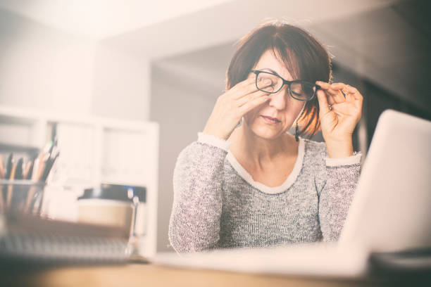 Tired middle age woman rubbing eyes stock photo