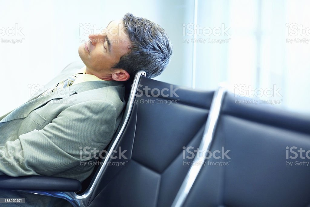 Tired middle aged business man resting in chair at airport royalty-free stock photo
