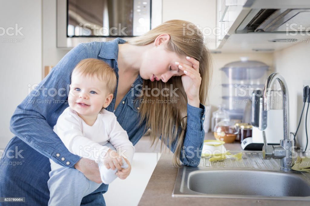Tired mom with baby in her arms standing by the sink stock photo