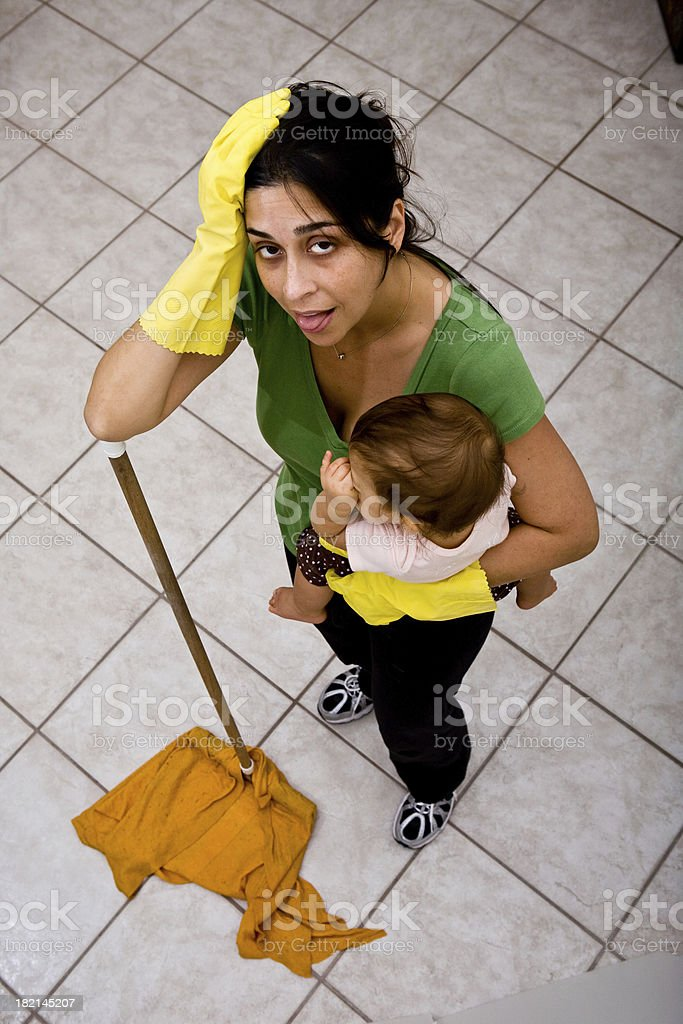 Tired mother holding baby and mopping the house