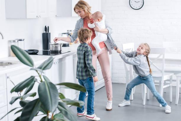 erschöpfte Mutter Kind Kind halten und unartige Kinder spielen in der Küche kochen – Foto