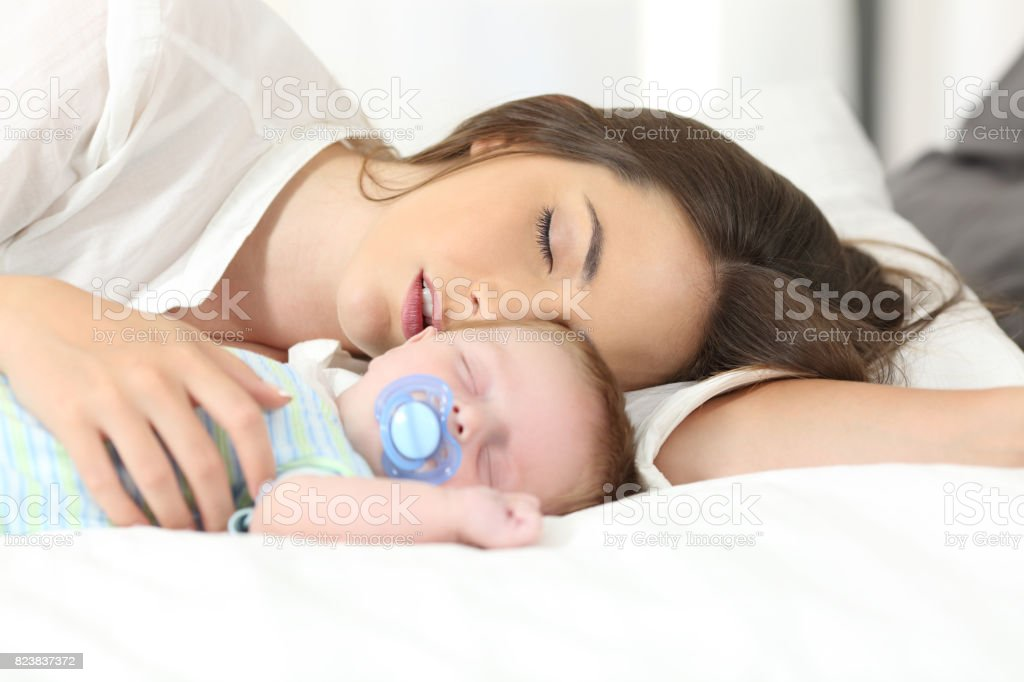 Tired mother sleeping with her baby stock photo