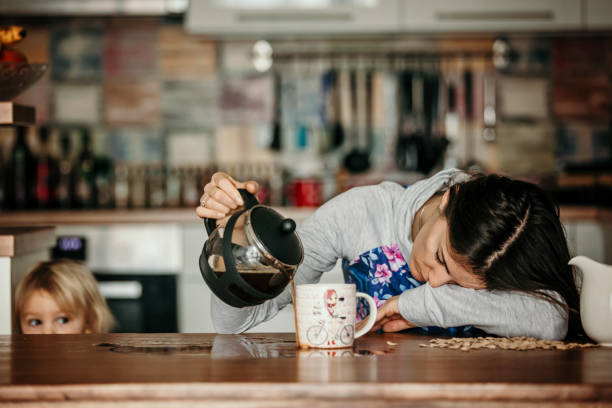 tired mother, trying to pour coffee in the morning. woman lying on kitchen table after sleepless night - desarrumação imagens e fotografias de stock