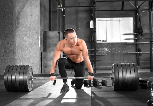 müde muskulöser mann mit einer langhantel im fitnessstudio. - mit muskelkater trainieren stock-fotos und bilder
