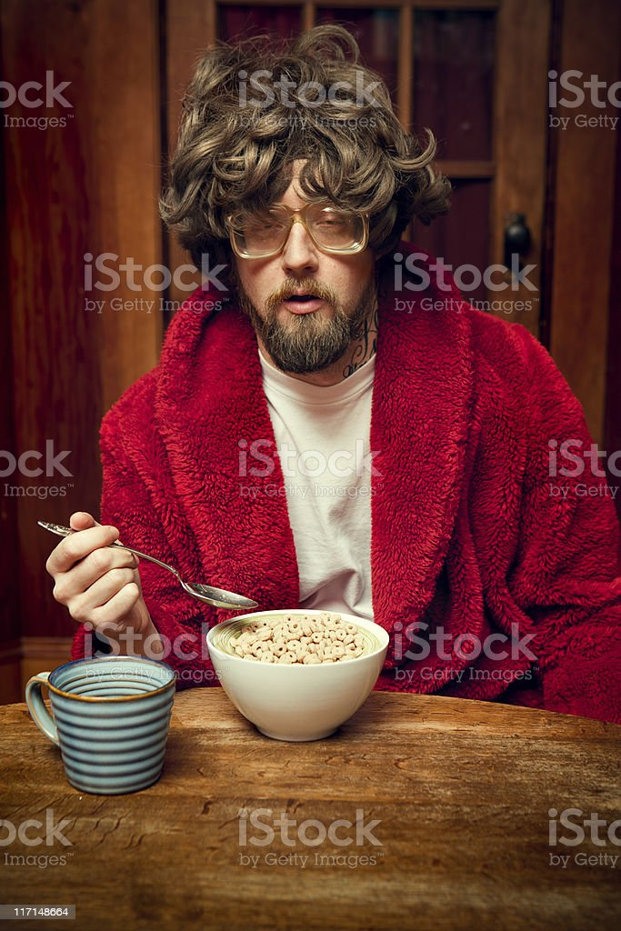 Tired Nerd Man Eating Cereal and Coffee stock photo