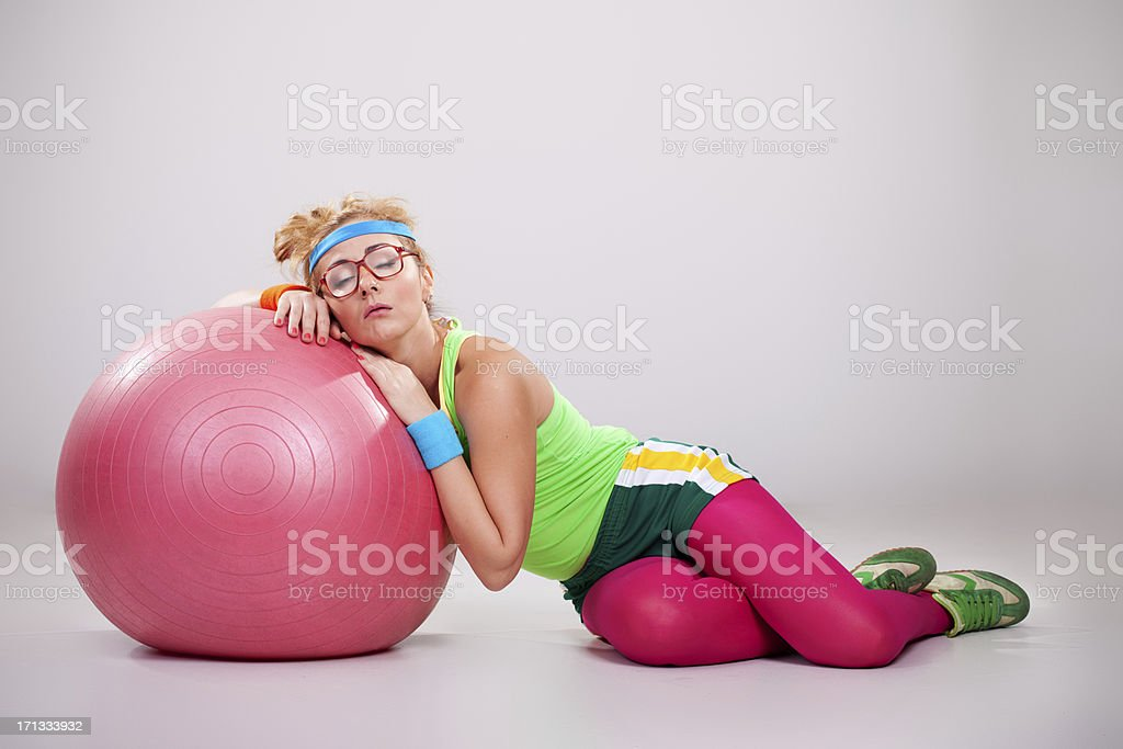 Tired nerdy fitness girl sleeping on pilates ball royalty-free stock photo