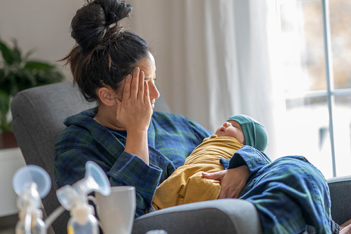 Tired mother holding her newborn child at home after tying to pump.
