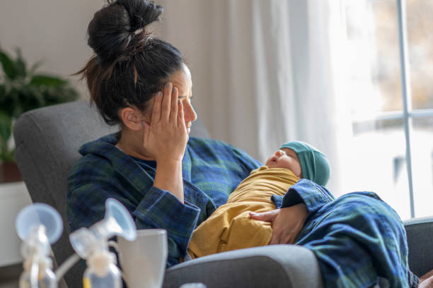 Tired new mother holding her baby stock photo