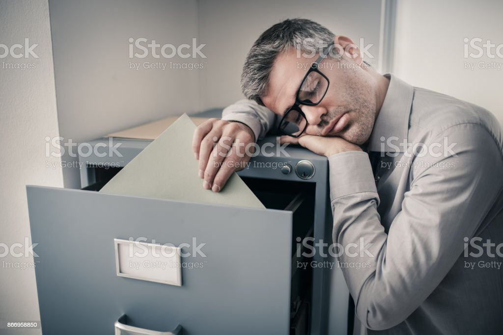 Tired office worker sleeping in the office stock photo