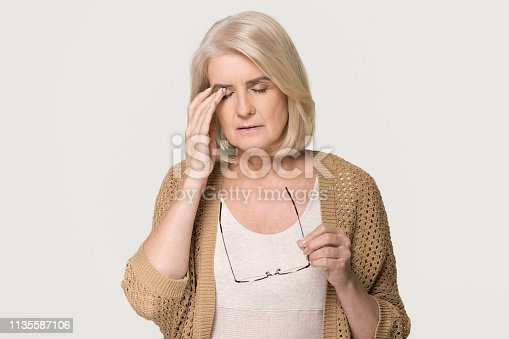 1049512672 istock photo Tired old woman holding glasses feeling eyestrain isolated on background 1135587106