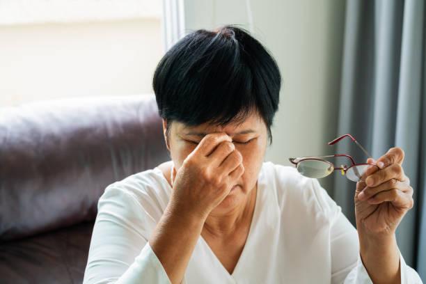 müde alte frau entfernen brillen, augen nach der lektüre papierbuch massieren. gefühl beschwerden wegen langer mit brille, augen schmerzen oder kopfschmerzen leiden - schwindelig stock-fotos und bilder