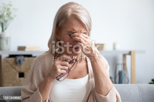 1049512672 istock photo Tired older lady suffering from dry eyes syndrome. 1251349992