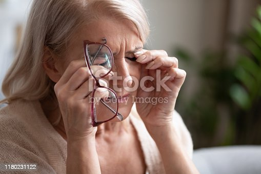 1049512672 istock photo Tired older woman taking off glasses, feeling eye strain 1180231122
