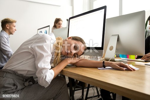 istock Tired or bored female employee lying asleep at office workplace 926375624