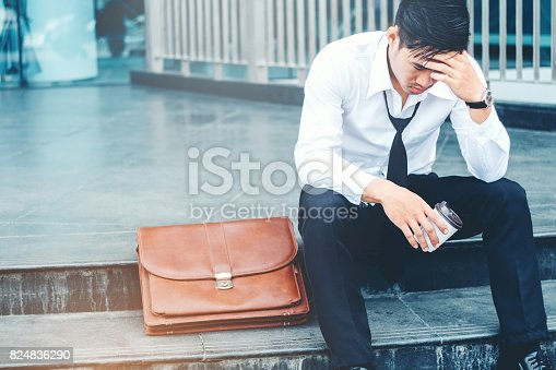 1018458132istockphoto Tired or stressed businessman sitting on the walkway after work Stressed businessman concept 824836290