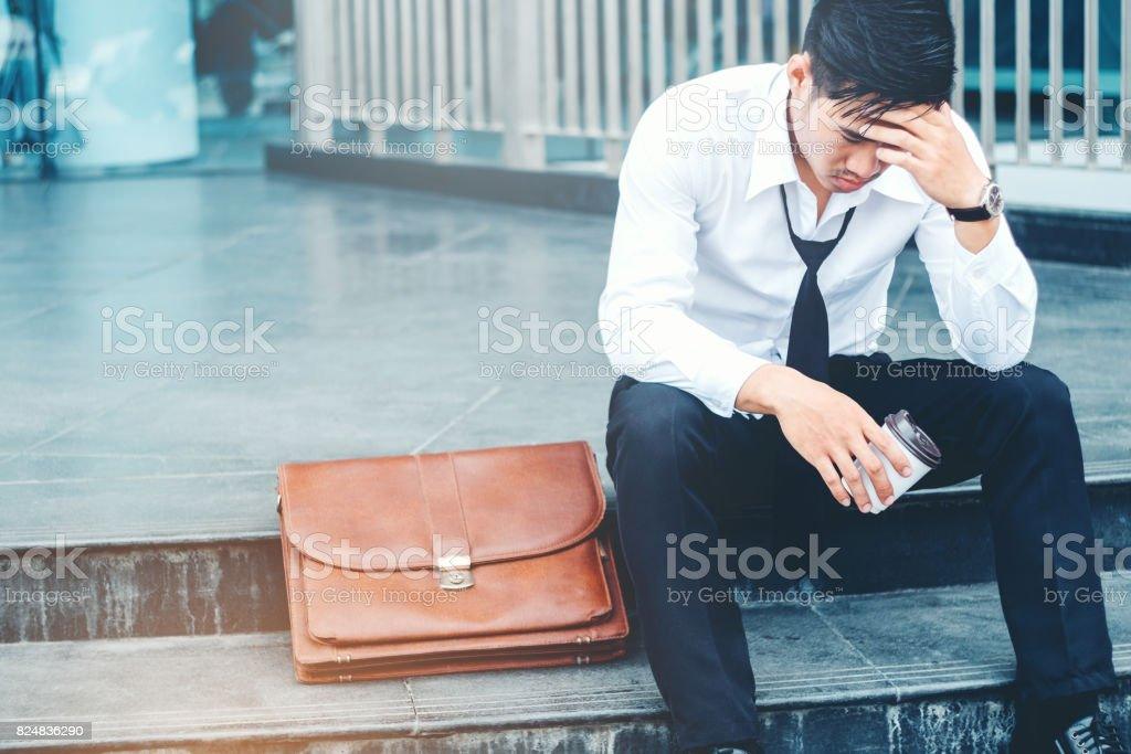 Tired or stressed businessman sitting on the walkway after work Stressed businessman concept stock photo