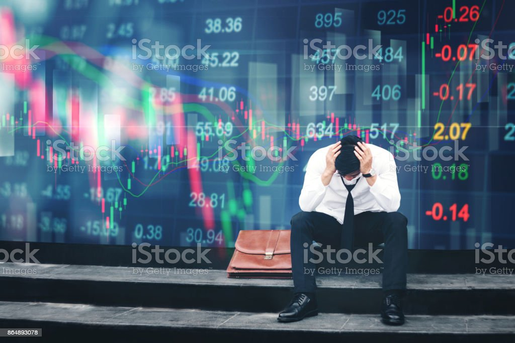 Tired or stressed businessman sitting on the walkway in panic digital stock market financial background stock photo