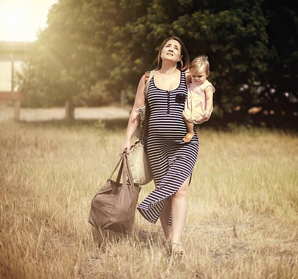 müde schwangere frau sie mit kleinkind sieht im sonne verzweifelt - kleinkind busy bags stock-fotos und bilder