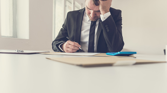 690496350 istock photo Tired overworked businessman sitting at his desk supporting his head with the arm 1130503431