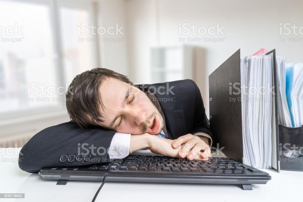 Tired overworked man is sleeping on keyboard in office at work. stock photo