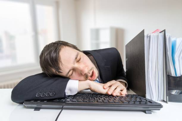 tired overworked man is sleeping on keyboard in office at work. - sleeping in work stock photos and pictures