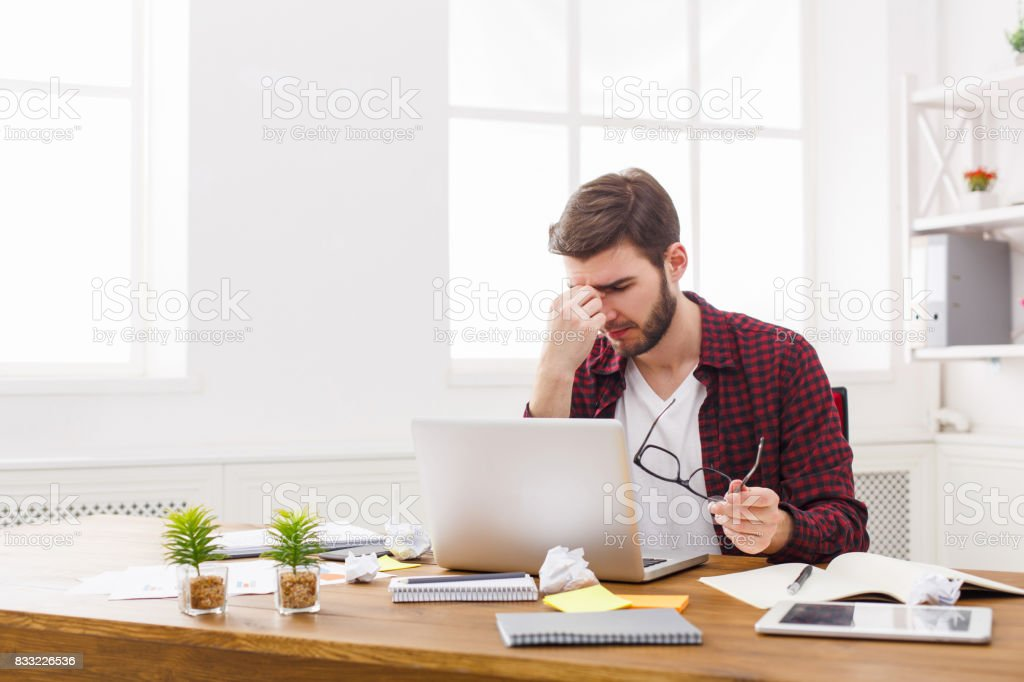 Tired, overworking businessman with laptop in modern white office stock photo