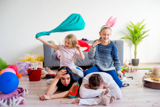 Tired parents and romping kids Tired parents lying on floor and their romping kids kids cleaning up toys stock pictures, royalty-free photos & images