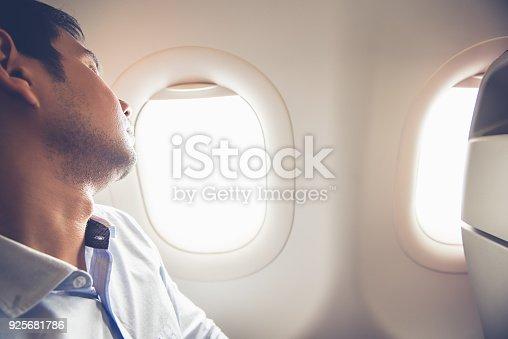 istock Tired passenger sleeping on the airplane at window seat 925681786