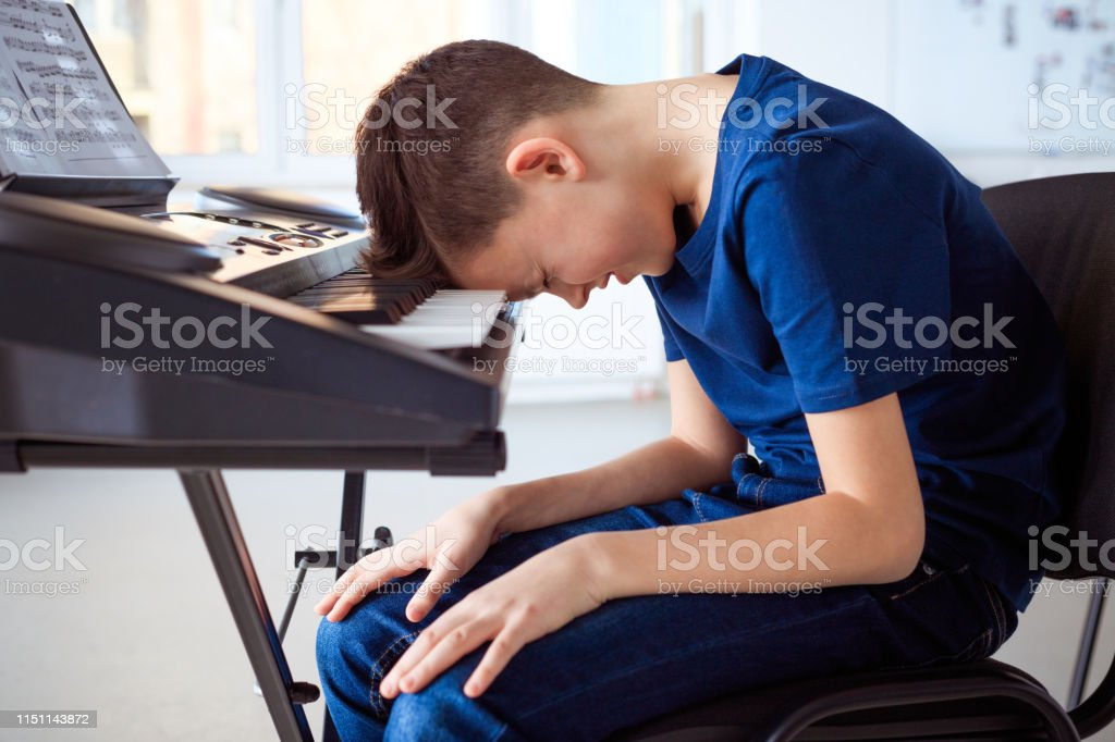 Tired pre-adolescent boy in piano class Tired pre-adolescent boy practicing piano. Student is frustrated while learning keyboard instrument. He is sitting in music class. 12-13 Years Stock Photo