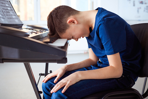 Tired Preadolescent Boy In Piano Class Stock Photo - Download Image Now
