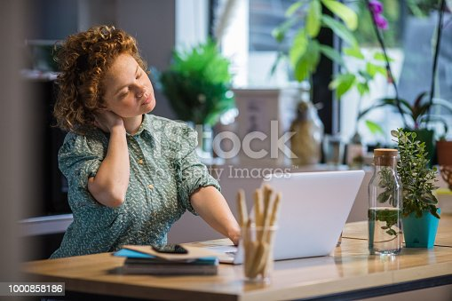 Young exhausted woman holding her neck while working on a computer at home.