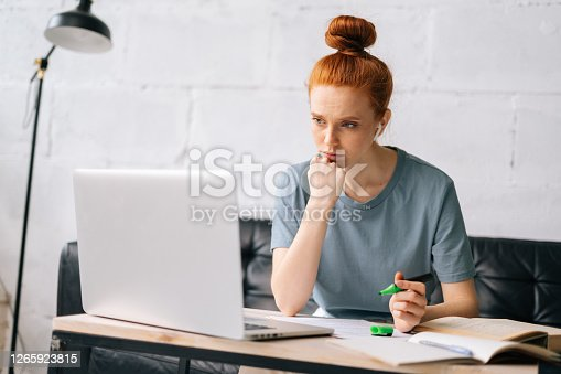 Tired redhead young woman is highlighting important things in paper documents. Worried business lady trying find solution of business problem. Focused girl student distance learning at home office.