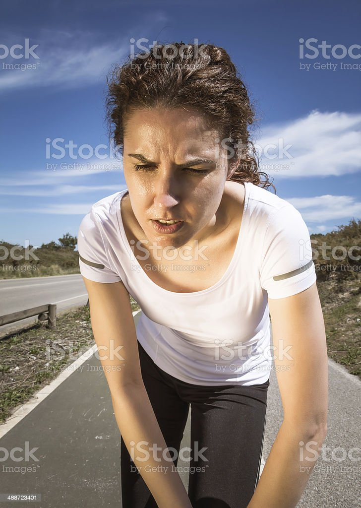 Tired runner girl sweating after running with sun stock photo