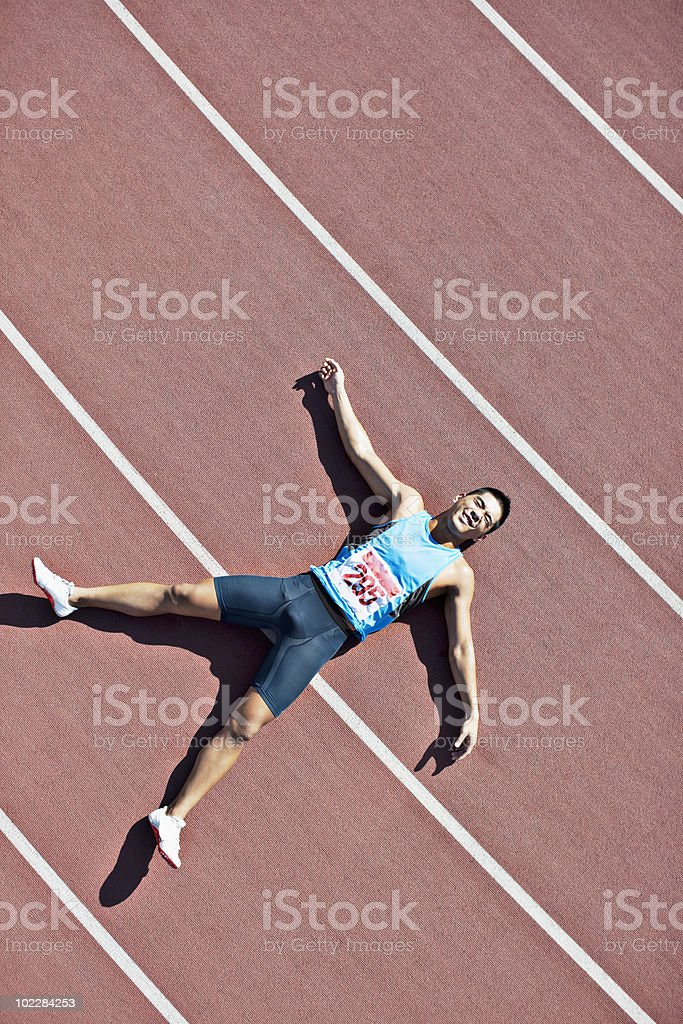 Tired runner laying on track stock photo
