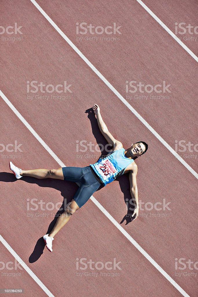 Cansado sentar on track runner - foto de stock