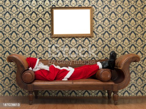 Tired Santa Claus lying on sofa,blank frame on wall