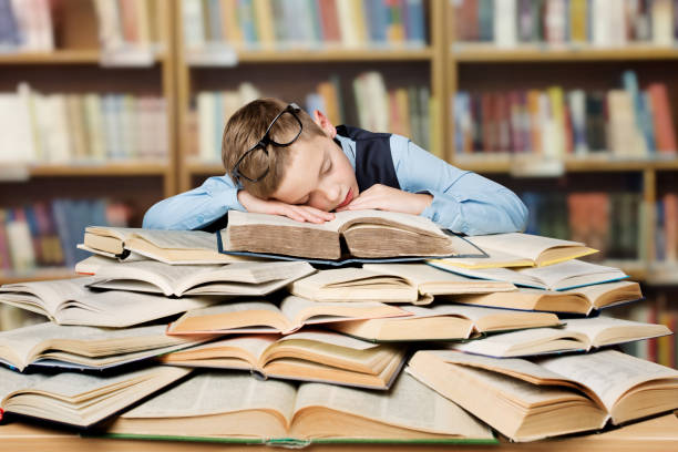 Tired School Child Sleeping on Books, Bored Boy Studying in Library, Hard Education stock photo