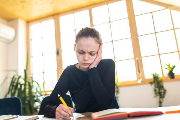 Müdes Schulmädchen, das Hausaufgaben macht – Foto