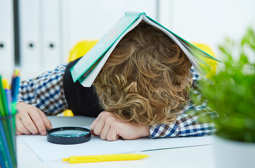istock Tired schoolboy is sitting at a desk with head on the table with the notebook on the head 927641492