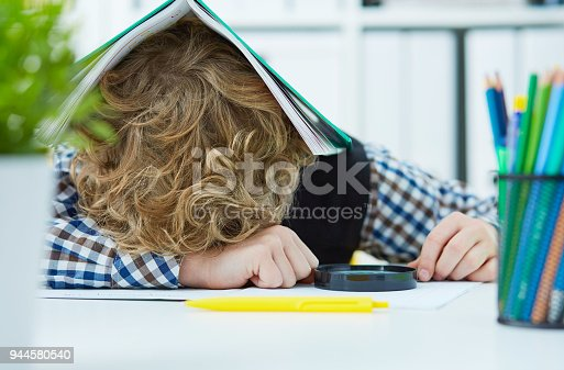 istock Tired schoolboy is sitting at a desk with head on the table with the notebook on the head 944580540