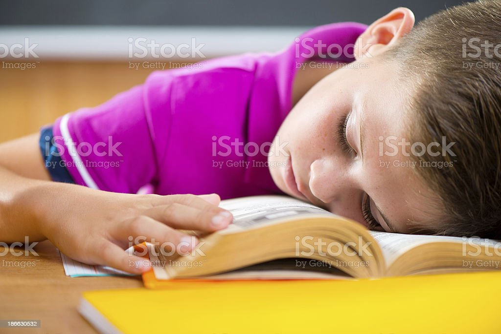Tired schoolboy sleeping on book royalty-free stock photo