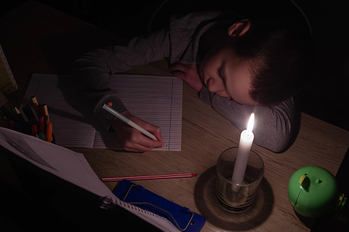 Tired schoolboy with candle in complete darkness doing homework. Power outage, blackout, concept image.