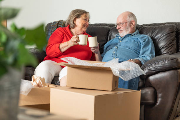 Tired Senior Adult Couple Resting on Couch with Cups of Coffee Surrounded with Moving Boxes stock photo