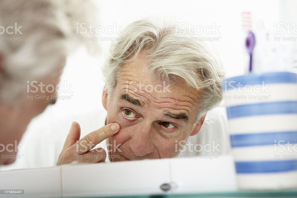 Tired Senior Man Looking At Reflection In Bathroom Mirror royalty-free stock photo