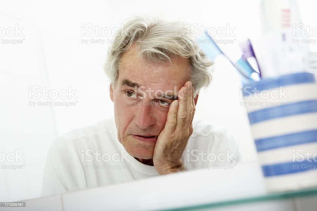 Tired Senior Man Looking At Reflection In Bathroom Mirror stock photo