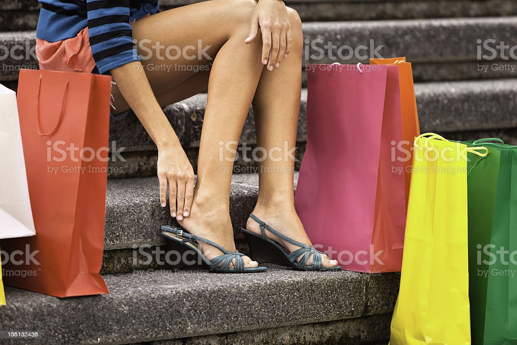 Tired shopping young woman resting and massaging her toes royalty-free stock photo