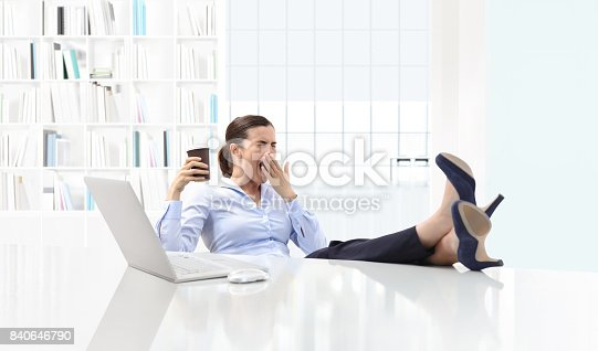 istock Tired sleepy business woman yawning, working at office desk and holding a cup of coffee, overwork and sleep deprivation concept 840646790