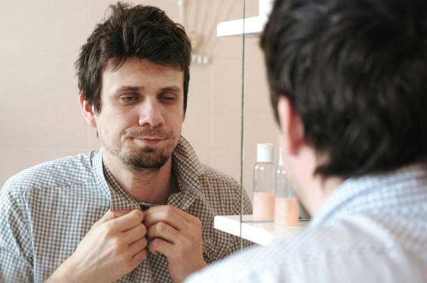 Tired sleepy man who has just woken up looks at his reflection in the mirror and sees his scruffy appearance, buttoning in a plaid shirt. stock photo
