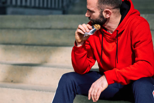 Tired sportsman sitting on stairs outdoors and eating energy bar. stock photo